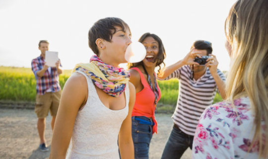 group of millennials, male taking picture of female blowing gum