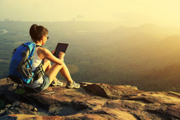 Woman On Mountain Top Researching How To Consolidate Credit Card Debt