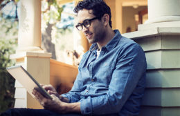 Man Browsing Internet On Tablet Researching Tips for Debt Consolidation