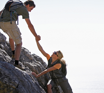 Man And Woman Climbing A Mountain
