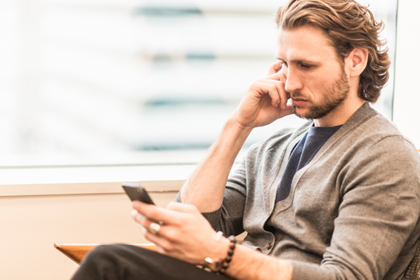 Man Reviewing Differences Between Fintech And Banks On Phone