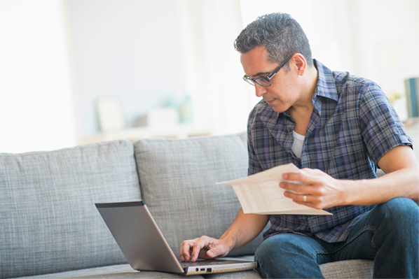 man searches laptop for personal loan tax deductions