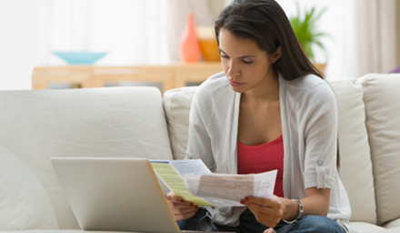Woman reviewing how to pay off debt with bills in hand