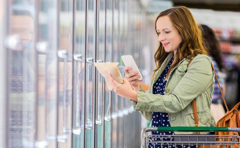 woman checks prices at grocery store - thumbnail