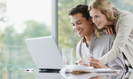 couple on laptop wonders what loans to pay off first
