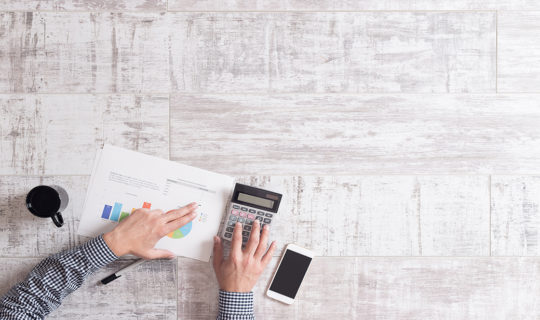 Man calculating finances on grey desk