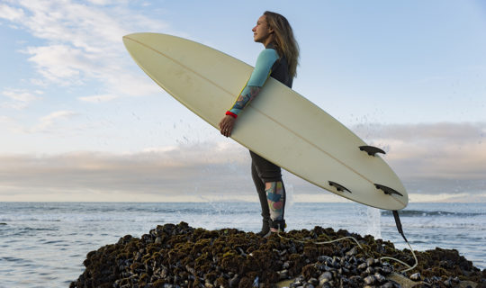 Surfer girl wearing wetsuit standing on top of ocean rock covered in mussels holding surfboard while waves are splashing against the rock.