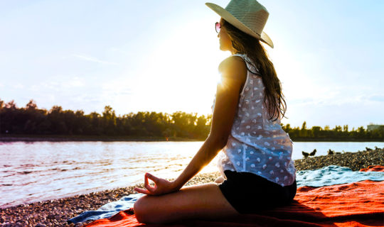 woman meditates near water