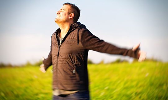 Man in field thinking of the best personal loan rates
