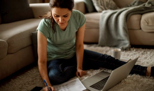 Woman in green shirt sitting in on floor with laptop and financial paperwork.