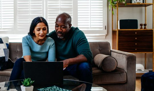Husband and wife using computer to research types of personal loans